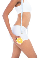 Close up of a fit woman wearing a tape measure around her neck a