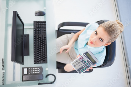 Overhead view of elegant businesswoman showing calculator
