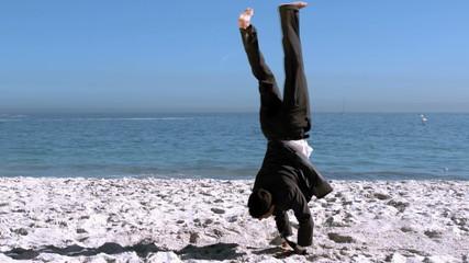 Businessman doing acrobatics on the beach