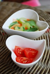 Vegetables salad in two heart shape bowls on natural background