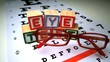 Red glasses falling next to blocks spelling out eye test