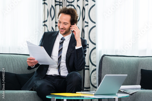 businessman in business hotel is on the phone