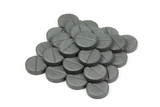 Activated charcoal tablets stacked pyramid on a white background
