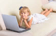 Little girl laying on the couch with laptop