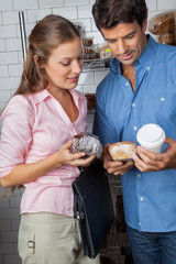 Couple Holding Cakes And Coffee Cup At Grocery Store