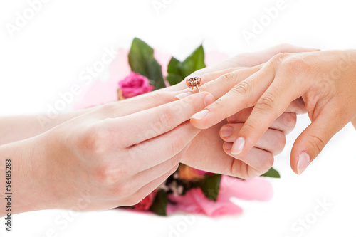 Man putting a golden ring on woman's hand
