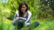 Woman sitting on grass writing on a notebook