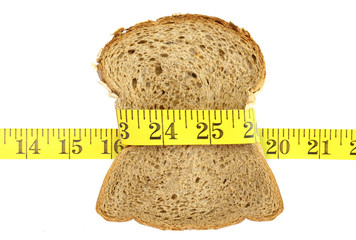 Wholesome slice of bread with measuring tape isolated on white