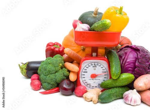 vegetables and kitchen scales closeup on a white background