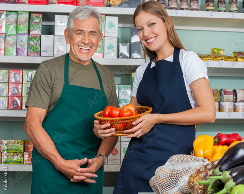 Saleswoman Holding Vegetable Basket With Male Colleague In Groce