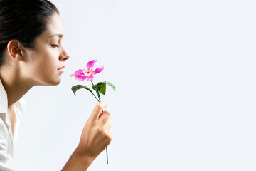 Profile photo of a beautiful girl smelling a flower