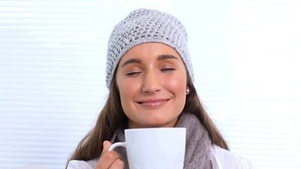 Young woman with hat and scarf smelling her cup