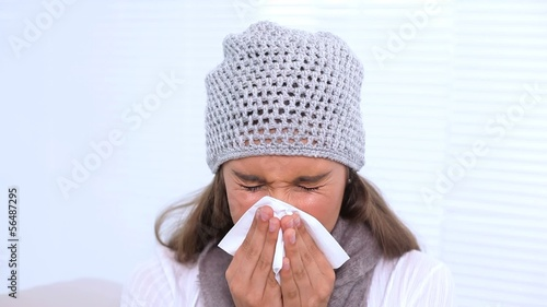 Young woman blowing her nose with tissue