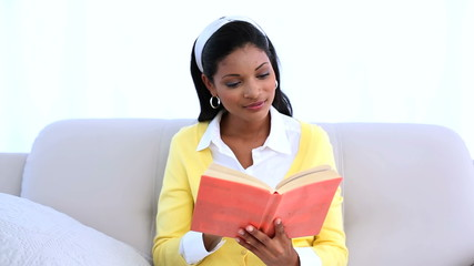Woman reading her book and looking at camera on sofa