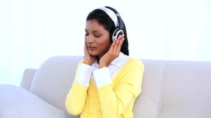 Woman wearing headphones for listening music on sofa