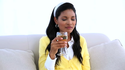 Woman sitting on sofa drinking white wine
