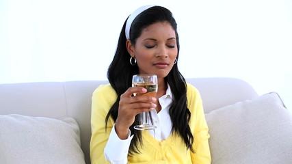 Woman sitting on sofa drinking white wine