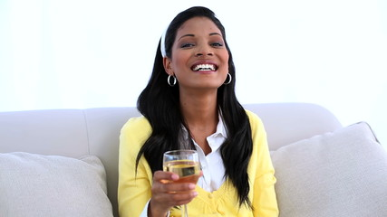 Smiling woman sitting on sofa drinking white wine