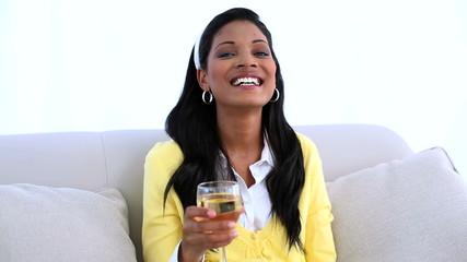 Smiling woman sitting on sofa drinking white wine