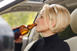 Young female driver drinking bear in the car