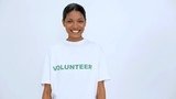 Volunteer woman smiling and does a thumb up at camera