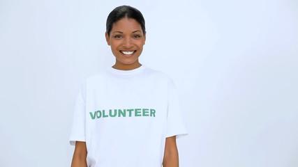 Volunteer woman smiling and does a thumb up at camera