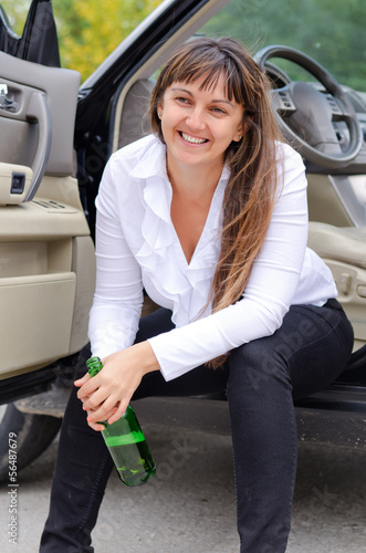 Happy woman drunkard in a car