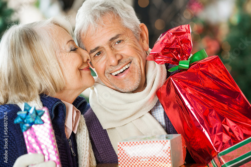 Woman About To Kiss Man Holding Christmas Presents