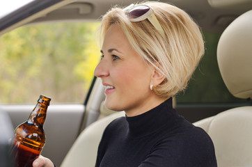 Young female driver drinking alcohol in the car