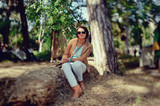 on nature near a tree on a haystack sits a woman in sunglasses
