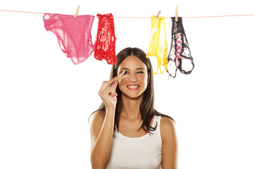 Attractive young woman posing next to clothesline with panties