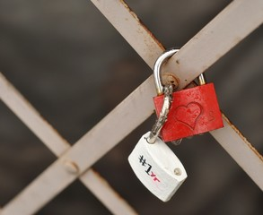 Love padlock tied to a fence. Heart shape. Red and white.