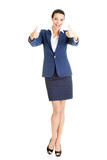 Smiling business woman with thumbs up gesture