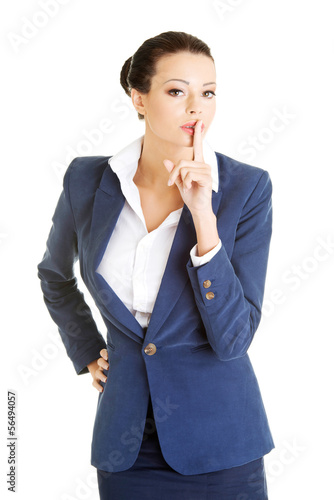 Attractive business woman with finger on lips