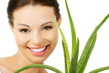 Young beautiful woman's face and aloe vera.