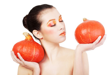 Woman with orange make up holding pumpkin