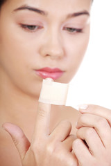 Preaty young woman using adhesive plaster