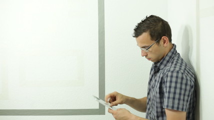 Young man with digital tablet leaning against wall