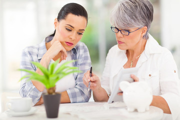 mid age mother helping daughter with her financial