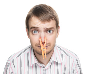 Man with orange clothespin on his nose - bad smell concept.