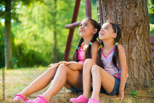 Hispanic sisters sitting under the tree and talking