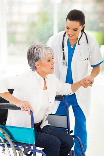 medical nurse helping senior woman on wheelchair