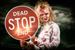 Halloween portrait. Scary zombie holding stop sign