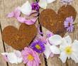 Rostige Herzen mit Blüten auf Holz