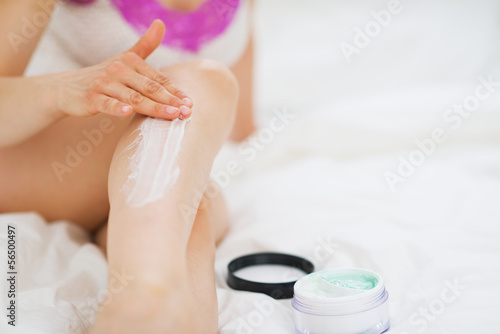 Closeup on woman applying creme on leg