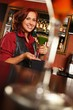 Cheerful barmaid with cocktail behind bar counter