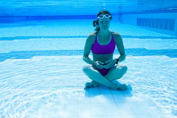 Female meditating underwater