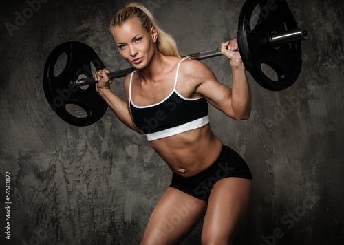 Beautiful muscular bodybuilder doing exercise with weights - 56501822