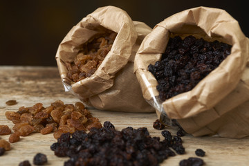 Golden and black raisins in paper bags on a wooden table