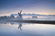 white Dutch windmill by river in misty sunrise
